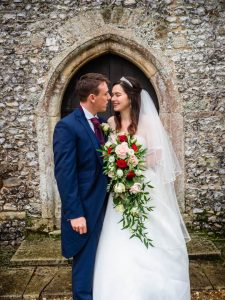 Bride and groom framed by a door arch outside an English country church