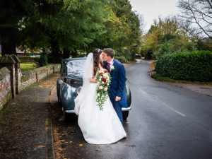 Bride and groom kiss in front of their wedding limousine outside an English country church