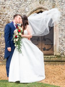 Bride and groom kiss outside an English country church while her veil billows behind her