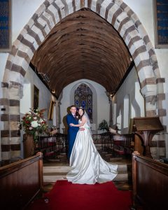 Bride and groom in the chancel of a country church