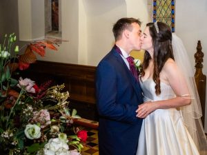 Bride and groom kiss in a country church