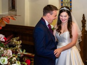 Bride and groom share a private joke while posing for photos in a country church