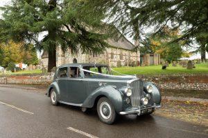Grey Bentley wedding limousine outside English country church