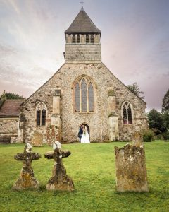 Bride and groom kiss outside an English country church