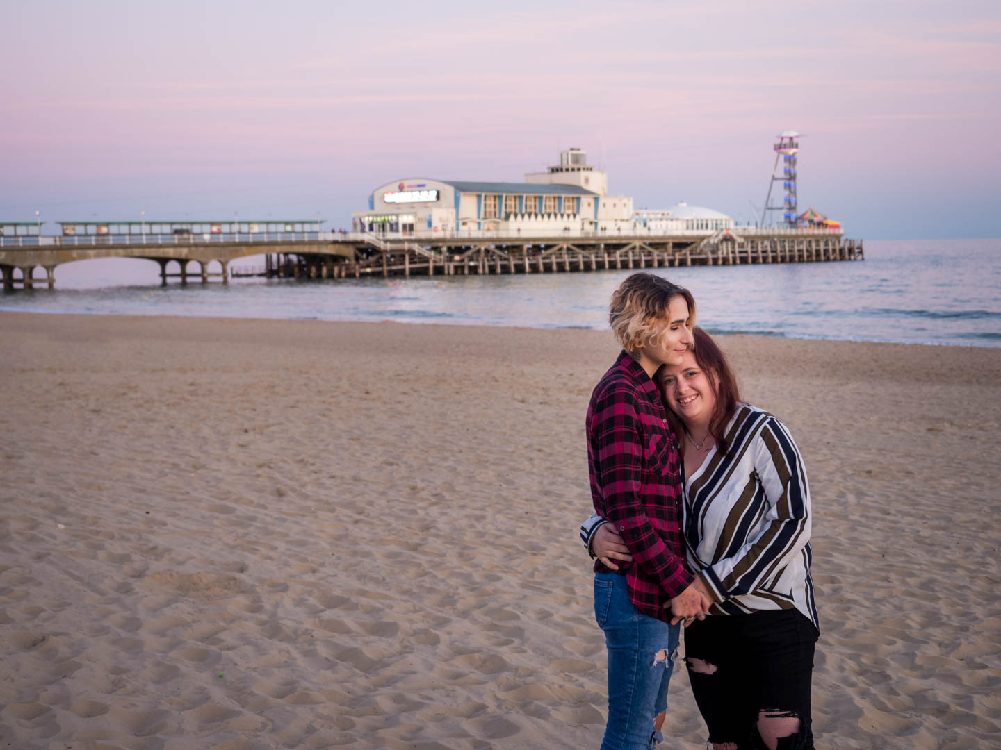 Lesbian couple embrace at dusk, with Bournemouth Pier in the background