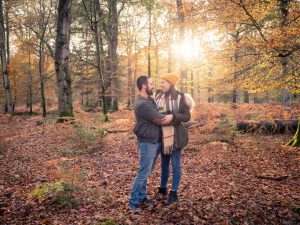 Smiling couple embrace in woodland, with the sun backlighting them and autumn leaves on the ground