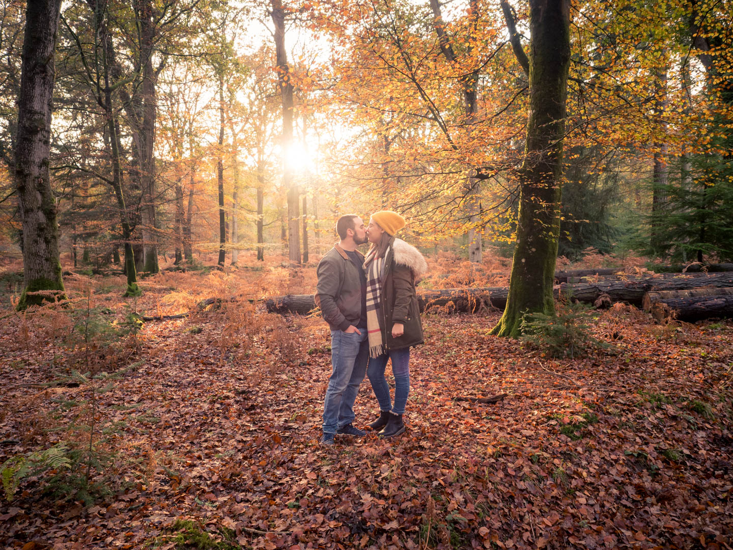 Couple kiss in woodland, with the sun backlighting them and autumn leaves on the ground