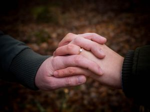 An engagement ring sparkles amid a couple's interwoven hands