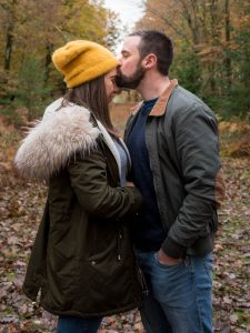 Man kisses woman on forehead with a woodland path receding into the distance
