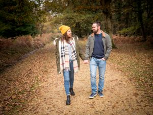 Couple walking hand-in-hand along a woodland track in autumn