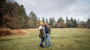 Couple stand in a woodland clearing, smiling, in autumn
