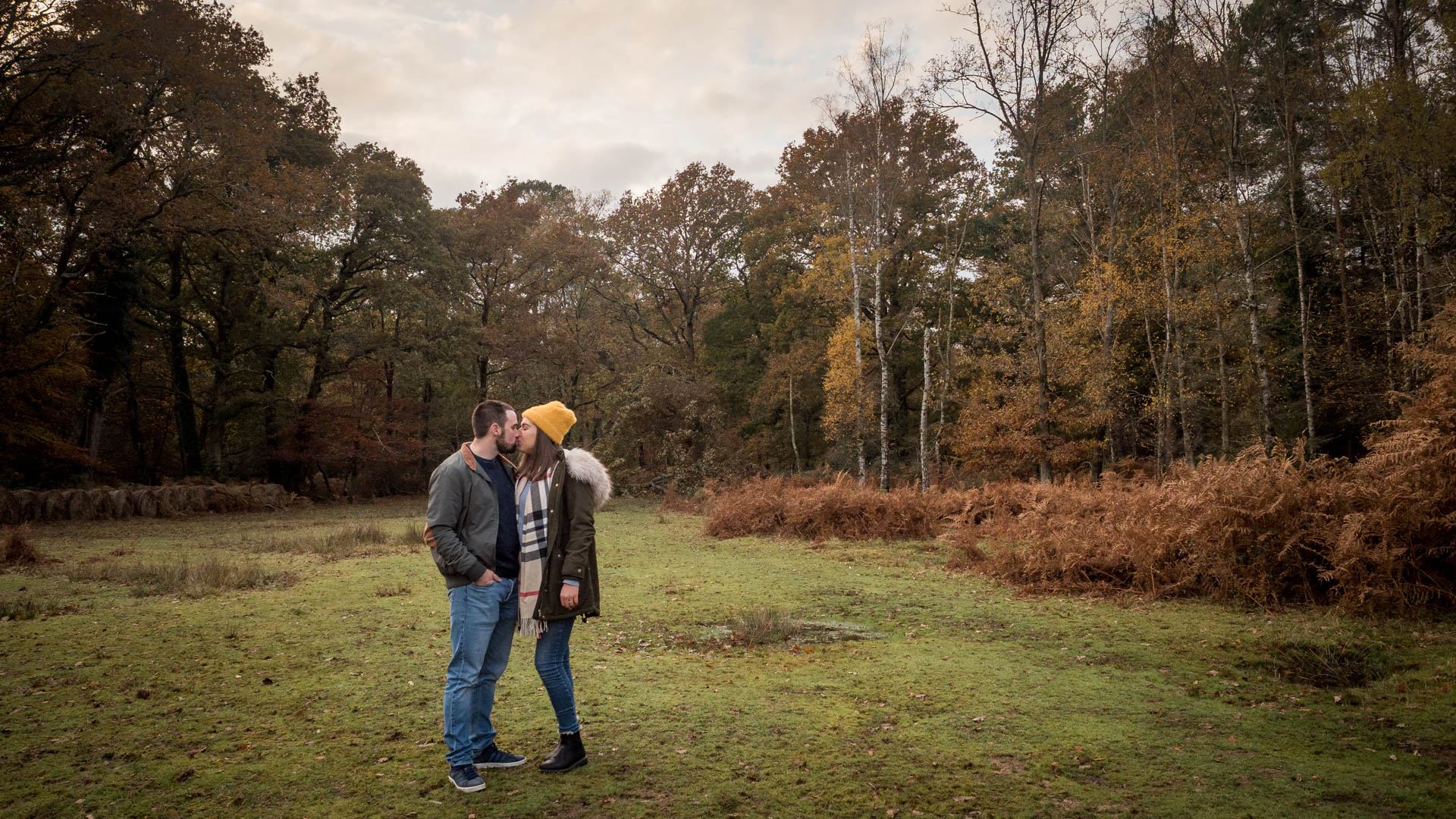 Couple kiss in woodland clearing, with a beautiful autumn sky in the background