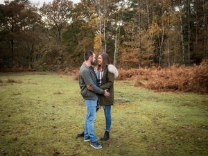 Couple stand, holding each other and gazing lovingly into each other's eyes, in a  woodland clearing