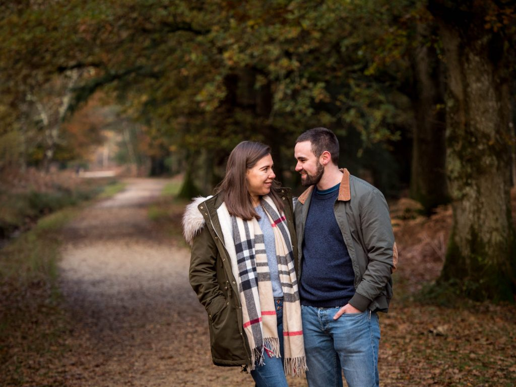 Couple smile at each other, with an woodland track receding into the distance behind them