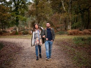 Smiling couple walking along a woodland track, the woman on her fiancé's arm