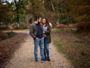 Couple standing on a woodland track, the woman holding onto her fiancé's arm