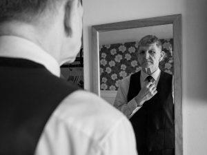 Bridegroom straightens his tie in front of bedroom mirror