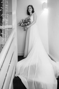 Bride and her train on the stairs at Sopley Mill