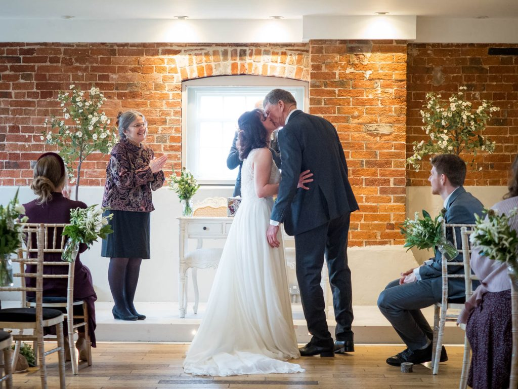 Bride and groom kiss during their wedding ceremony at Sopley Mill