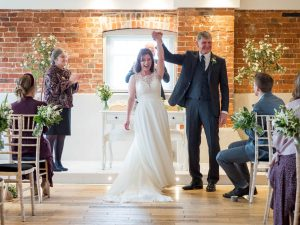 Bride and groom enjoy applause during their wedding ceremony at Sopley Mill