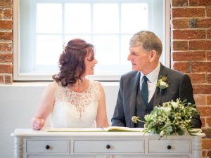 Bride and groom smile at each other while seated to sign the registers during their wedding at Sopley Mill