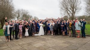Bride, groom and their guests wave outside after getting married at Sopley Mill