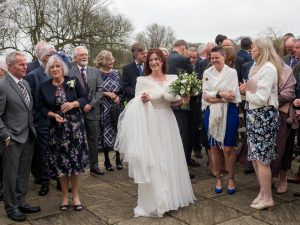 Smiling bride surrounded by guests after the big formal wedding photo at Sopley Mill