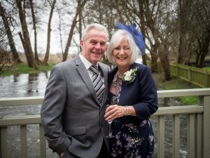 Smiling couple of wedding guests on the bridge at Sopley Mill
