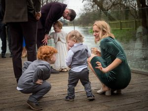 Mother crouches down to talk to her children during drinks after wedding at Sopley Mill