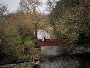Bride and groom kiss on the old railway bridge near Sopley Mill