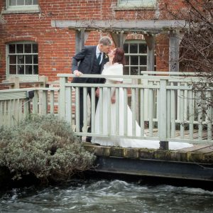 Bride and groom about to kiss on the bridge outside Sopley Mill