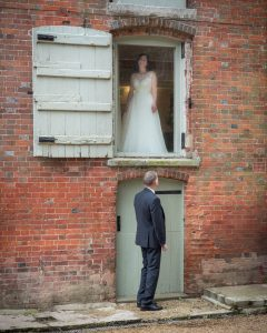 Groom looks up at bride, who has appeared in the first-floor window at Sopley Mill