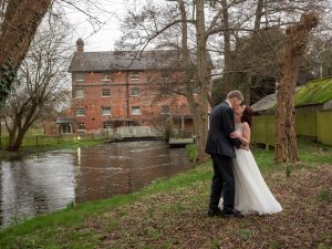 Bride and groom kiss on the river bank outside Sopley Mill