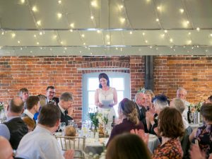 Bride smiles at guests while delivering her speech during wedding breakfast at Sopley Mill