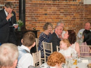 Groom smiles to bride while making his speech during wedding breakfast at Sopley Mill