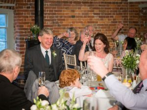 Bride and groom laugh during toasts at their wedding breakfast at Sopley Mill