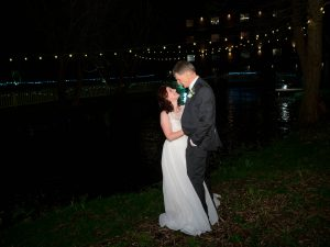 Bride and groom on the river bank outside Sopley Mill at night
