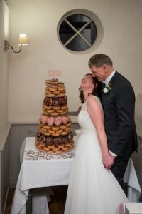 Bride and groom laugh next to their 'cake', a tower of iced doughnuts, at Sopley Mill