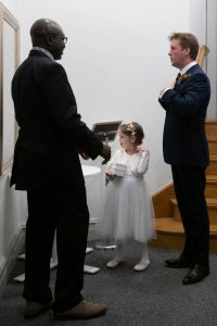Little bridesmaid admires herself in the mirror as her father straightens his tie