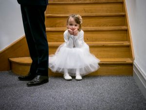 Little bridesmaid sits on a bottom step with her father's legs in shot giving a sense of scale