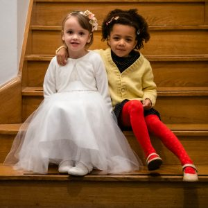 Little bridesmaid in white dress with friend in red tights and yellow cardigan sitting on wooden stairs