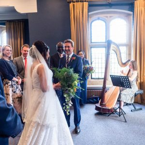 Groom looks delighted as bride arrives in Winchester Registry Office ceremony room while harpist plays