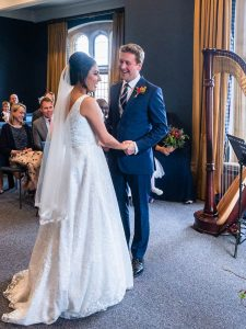 Bride speaks as groom in blue suit holds her hand and smiles
