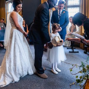 Little bridesmaid shows box containing wedding rings to the registrar as the bride, groom and best man look on