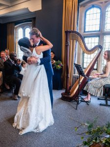 Bride and groom kiss passionately as guests applaud during their wedding ceremony