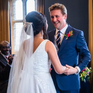 Groom in blue suit smiles broadly at bride during wedding ceremony