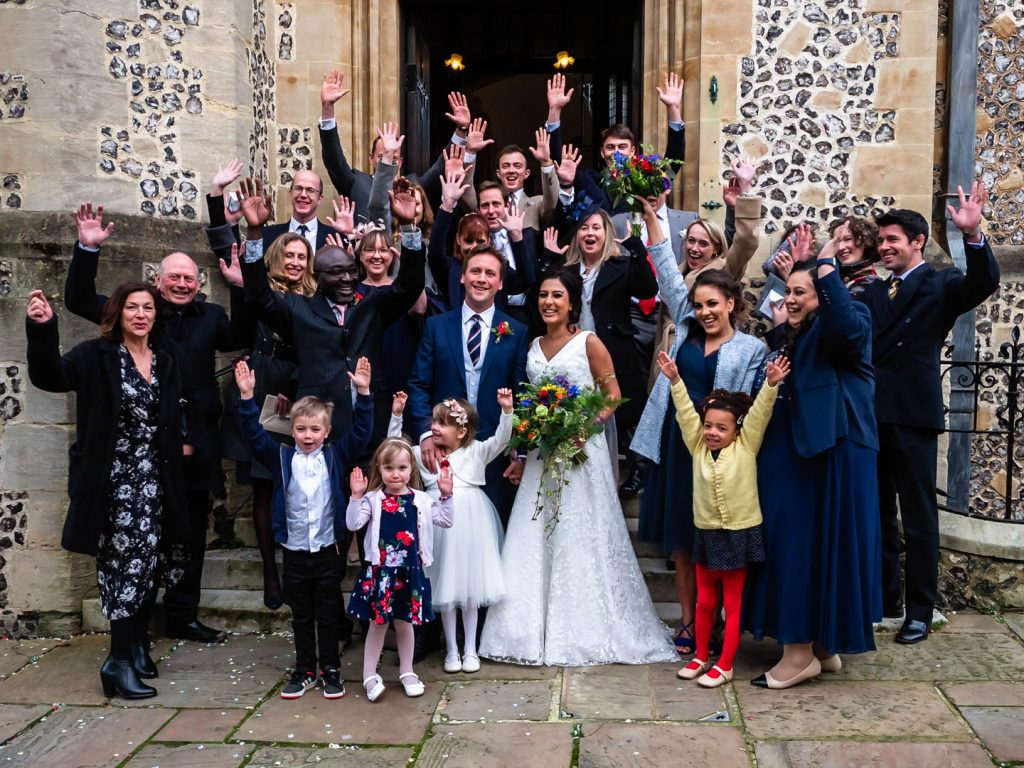 Wedding party waves for the camera outside Winchester Registry Office