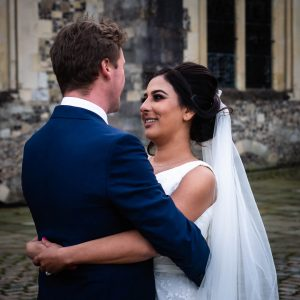Bride smiles at groom as they hold each other outside Winchester's Great Hall