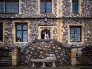 Bride and groom kiss at the top of steps in front of a Victorian Gothic flint-faced building