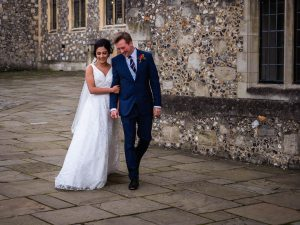 Bride walks on the arm of her new husband pased Victorian Gothic flint-faced buildings